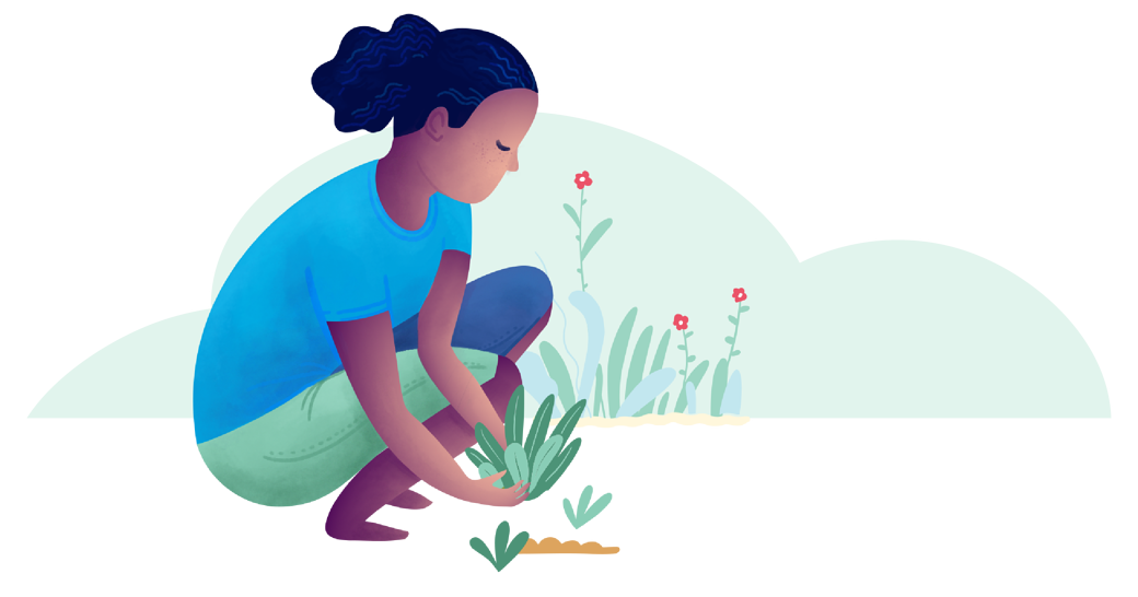 A person crouches beside a patch of soil, lowering a small plant into the ground